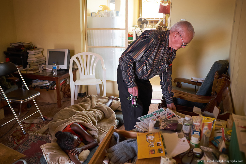 Father Hermann's Apartment, Windhoek, November 30, 2013. Father Hermann gives shelter to a woman who knocked on the door of his apartment late at night, looking for help. When in adversity, the women often come to Father Hermann's home at the Catholic Church in Pioneers Park, Windhoek. Due to the alarming extent of his work and serious health issues the priest has more and more difficulties to keep his apartment clean and tidy.