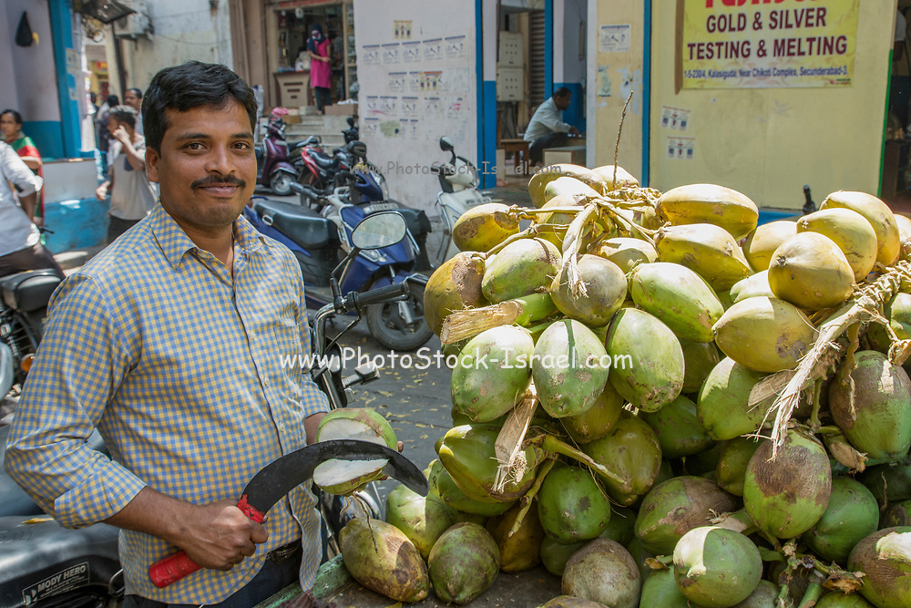 Coconut seller at an Indian Market. Photographed in Ahmedabad, Gujarat, India