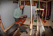 Man hand weaves a woollen rug on a loom at a Handicraft shop in Madaba Jordan