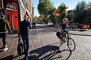 In Utrecht passeren een bellende man en een bellende vrouw op de fiets elkaar.<br /> <br /> In Utrecht a man calling passes a woman calling on a bicycle.