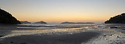 Sunset falls over Kikowhakawere Bay, just north of Coromandel, on the Coromandel Peninsula, New Zealand.
