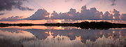 The calm waters of Nine Mile Pond reflect a typically spectacular Florida sunrise