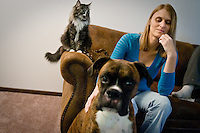 JEROME A. POLLOS/Press..Melissa Rogers sits on her couch in her Coeur d'Alene apartment Friday with her cat Smeagol and 5-year-old boxer Sullivan. Rogers, who owns a total of four pets that were prescribed by her doctor as companion pets, has had a difficult time finding housing that would accept the service animals.