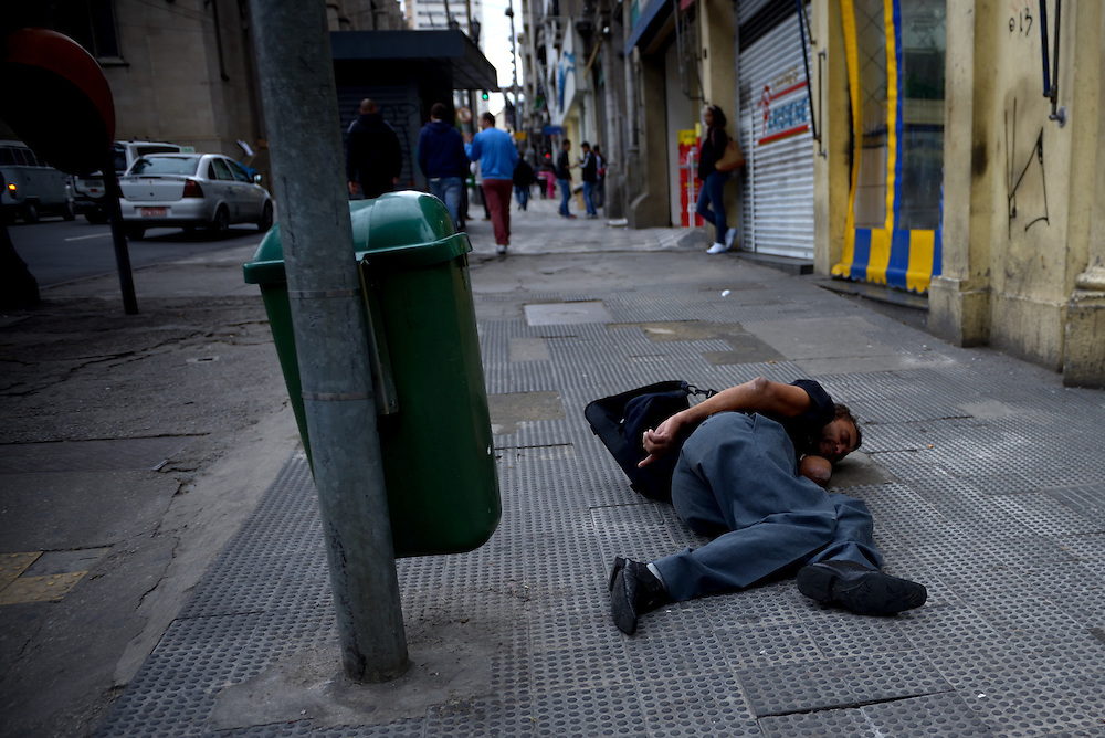 A Brazilian homeless is sleeping on a pavement in a street in central Sao Paulo on June 19, 2014. <br />