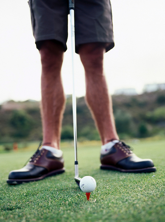 Close up of a man preparing to tee-off on the golf course