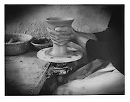 Potter fashions a ceramic object on a foot-powered potter's wheel, in the fort headquarters for Turquoise Mountain Foundation, Kabul, Afghanistan. The foundation is actively supporting the resurgence of indigenous handicrafts in Afghanistan.