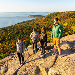 """A group of hikers pose on a ledge on """"The Beehive"""" in fall in Maine's Acadia National Park."""