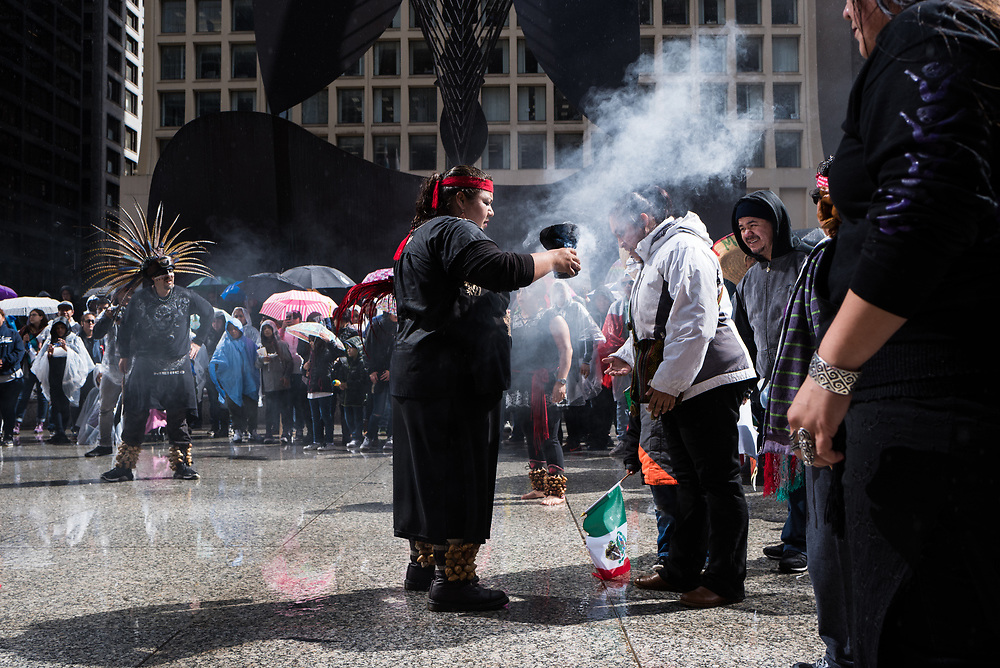 Dancers perform a ceremonial smudging at a May Day rally in Daley Plaza in Chicago on May 1, 2017.