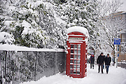 A traditional red telephone box is seen on Denmark Hill, South London covered in fresh snow from overnight snowfall. Pedestrians walk past next to Ruskin Park, SE24.  These K-series kiosks were designed in 1936 by the renowned designer Giles Gilbert Scott. With the increasing use of mobile phones the static phone boxes are still used in remote areas of the UK where mobile service is still patchy and in major towns and cities, their presence is becoming rarer. In rural regions however, the British red phone box is still a delight to see and use.