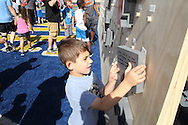 "Samuel Dickson, 6, of Centerville, places a block with a personal message on the ""Better Wall"" during the All Pro Dad Father & Kids NFL Experience at Welcome Stadium, Saturday, June 18, 2016."