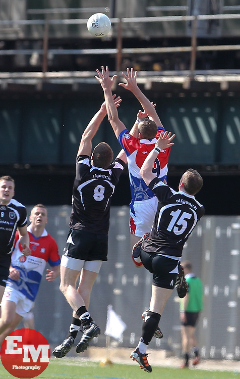 May 6, 2012; Bronx, NY; USA;  New York's Eoghan Carew leaps for the ball while being defended by Sligo's Tony Taylor (8) and Mark Breheny (15) during their game at Gaelic Park in the Bronx, NY.