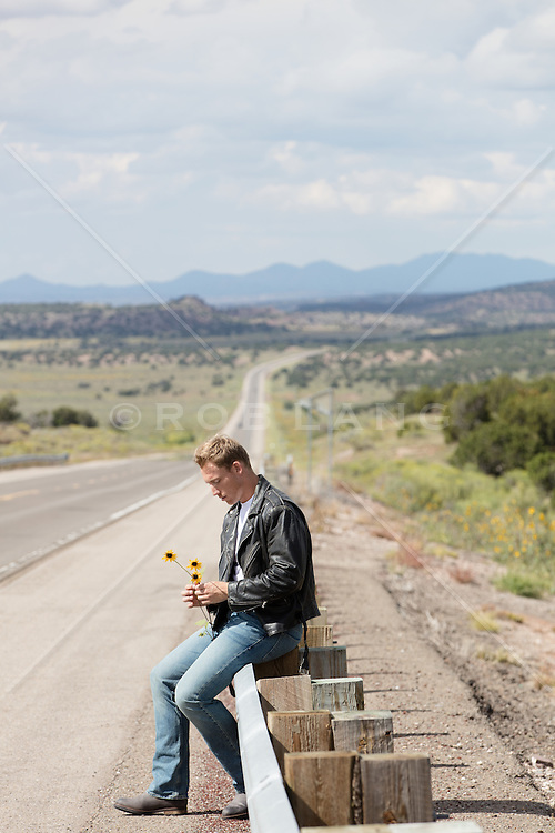man holding flowers on the side of a long road