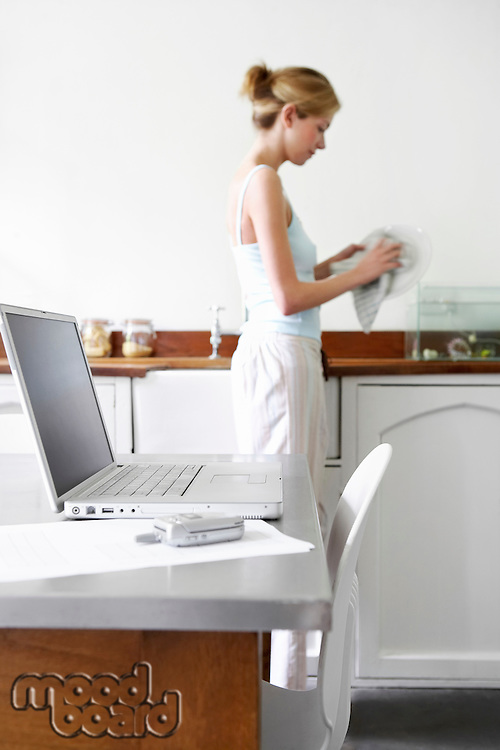 Young woman washing dishes in kitchen by laptop and cell phone