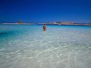couple in the sea near the Torre della Pelosa<br /> at Stintino, Sardinia Italy