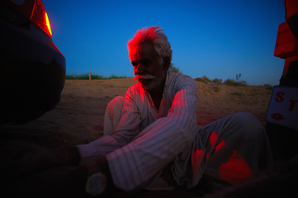 An old man tying a car, which was stuck in the desert, to his jeep to get it out of the sand, Jodhpur, Rajasthan.