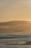 A floatplane rises into the sunset from the harbour of Victoria, BC