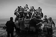 Refugees from Afghanistan and Syria disembark from a discarded life boat on the northern shores of Lesbos near Skala Sikaminias, Greece on 10 November, 2015. Lesbos, the Greek vacation island in the Aegean Sea between Turkey and Greece, faces massive refugee flows from the Middle East countries.