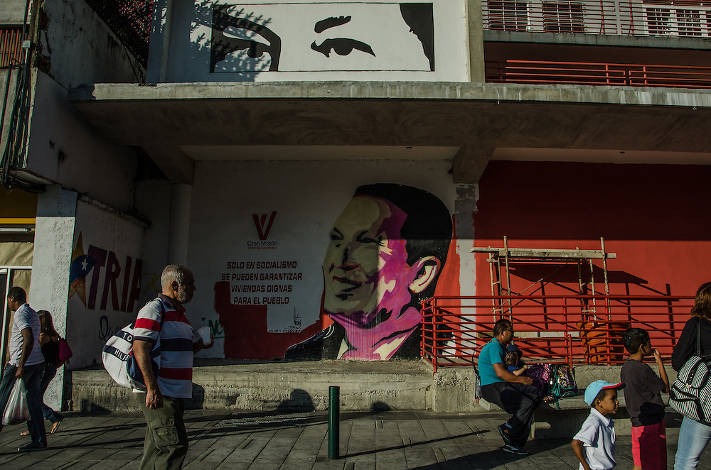 "CARACAS, VENEZUELA - JANUARY 18, 2016:  People walk past murals of the former President of Venezuela, Hugo Chávez, painted on the side of a government housing building, with a quote that says in Spanish: ""Only Socialism can guarantee dignified housing for the people."" Chávez built thousands of government housing projects, like this one in the Bellas Artes neighborhood of Caracas. He gave supporters the keys, and they gave him their votes. But there was one thing Mr. Chávez never handed over: The property titles that would allow them to cash out. Now that Mr. Chávez is dead and Venezuela's opposition has taken its parliament, it is in these deeds that they see a possible first step in dismantling Mr. Chávez's movement. After taking power of the National Assembly this month for the first time in 16 years, the opposition carted away the portraits of Mr. Chávez from government halls, drafted a proposal to free the politicians jailed by socialists and has even threatened to recall President Nicolás Maduro. Now they want to transfer the deeds of the homes Mr. Chávez built to the country's poor—and with them, possibly, the loyalties of those who live there for years to come.  PHOTO: Meridith Kohut for The New York Times"