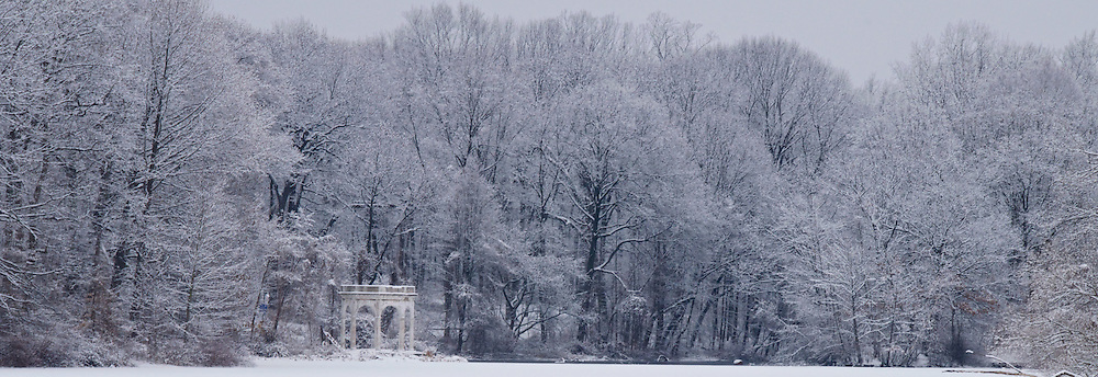 Snow covered trees provide scenic backdrop to gazebo along frozen lake in Yonkers' Tibbets Brook Park in Westchester County, New York