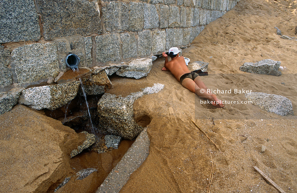 Next to a beach bather, water pours from an outlet pipe on a tourist beach on Coloane island Cheoc Van beach, Macau, China.