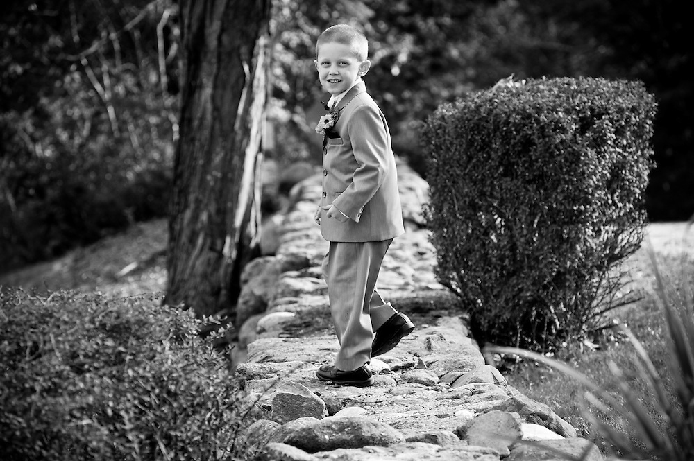 The ring bearer runs down a stone wall before the wedding ceremony at the Dexter Inn, Sunapee, NH.