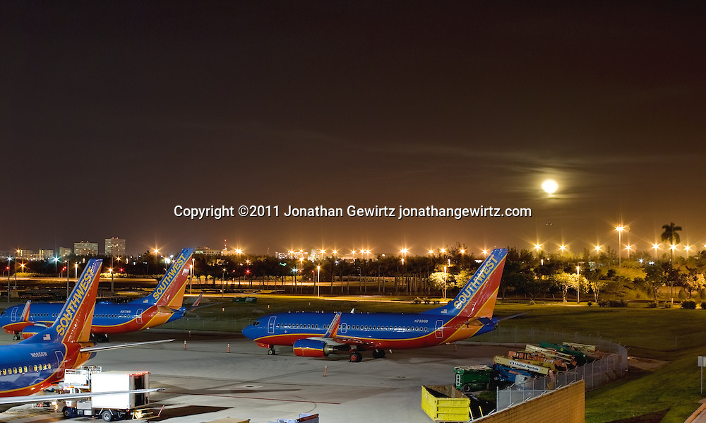 Southwest Airlines aircraft parked at Fort Lauderdale-Hollywood International airport at night with a full moon in the background. WATERMARKS WILL NOT APPEAR ON PRINTS OR LICENSED IMAGES.