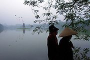 Two women go for their morning walk around Hoan Kiem Lake, in Hanoi's historical centre. (The turtle tower can be seen in the lake too).