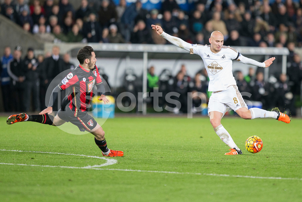 Jonjo Shelvey of Swansea shoots at goal under pressure from Adam Smith of Bournemouth during the Barclays Premier League match between Swansea City and Bournemouth at the Liberty Stadium, Swansea, Wales on 21 November 2015. Photo by Mark Hawkins.