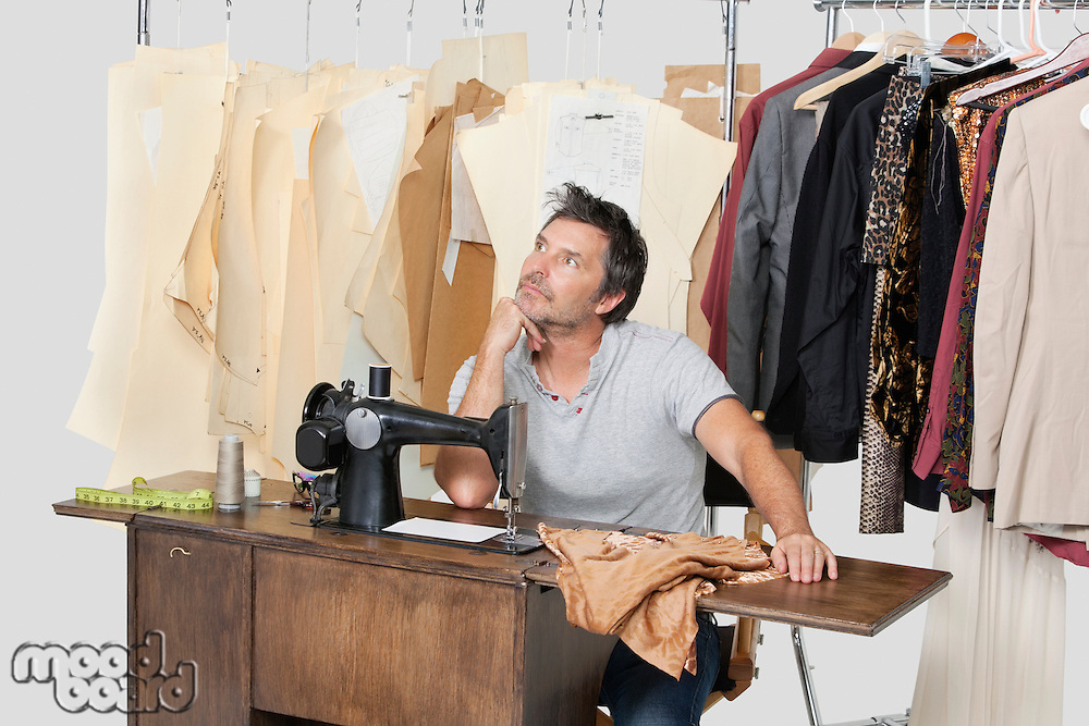Mature male tailor thinking while sitting at sewing machine with fabric