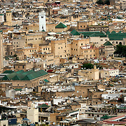 This view of the medina (old city) of Fez was taken from the hills outside of the medina.  Fez is located between the Rif mountains and the Atlas mountains in northern Morocco.  It's a beautiful area and the views of the area are quite beautiful, particularly in the spring.<br /> <br /> The Holy City of Fez, a jewel of Spanish-Arabic civilization, is an outstanding and well-preserved example of an ancient capital of the Almoravids and the Almohads in the North African context, despite the destruction of the city and the transfer of the capital to Rabat. The Medina of Fez in its old, densely packed monuments - madrasas, fondouks, palaces, residences, mosques and fountains - is the memory of the capital founded in year 192 of the Hegira (808) by Idriss II.<br /> <br /> The ancient city, home to the oldest university in the world, is composed of two distinct centres. One is the quarter of the Andalous, a population that fled from the Umayyad masters of Cordoba and who came to settle definitively on the right bank of the Fez. The other is the quarter of the Quarawiyyia, a people emigrated from Kairouan in the 11th century who chose the left bank of the river to develop their activities.<br /> <br /> Despite the destruction of a considerable part of the city by the Almoravids, the dynasty that took power in the 11th century, the two quarters grouped around two major monuments, the Jama el Andalous (the Mosque of the Andalusians) and the mosque of El Karaouiyne, have preserved their identities intact in the old city of Fez el Bali.<br /> <br /> In the 13th century, after the Merinid conquest, when the city found itself constrained within its walls, a new city, Fez el Jedid, was founded directly to the west, in ah 674 by the sultan Abou Youssouf. It replaced Marrakesh as the capital of the kingdom. In the 14th century a Jewish quarter, the Mellah, was joined to the newly founded city. The urban fabric and the principal monuments in the Medina date from this period.<br /> <br /> Since then, the twin cities have led a symbiotic exist