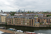 New homes near the Regent's canal with a view of the City of London on the horizon.