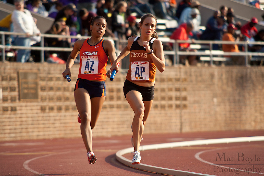 Members of the University of Texas and the University of Virginia near the end of the turn during the College Women's Distance Medley College at the 2010 Penn Relays at Franklin Field.