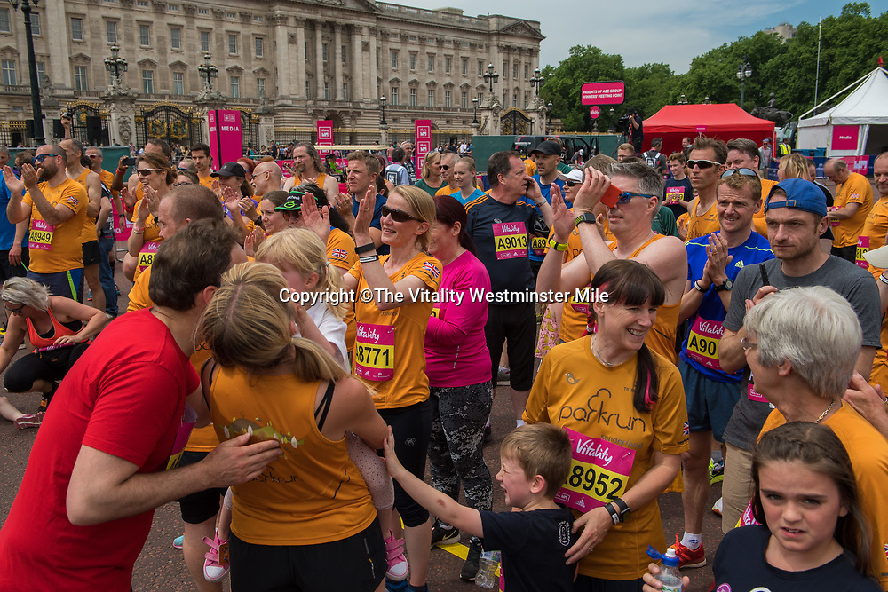 Runners in the Park Run wave at the finishing line outside Buckingham Palace at The Vitality Westminster Mile, Sunday 28th May 2017.<br /> <br /> Photo: Thomas Lovelock for The Vitality Westminster Mile<br /> <br /> For further information: media@londonmarathonevents.co.uk