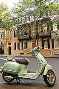 A Vespa scooter parked outside a historic home with decorative ironwork on Church Street in Charleston, SC.
