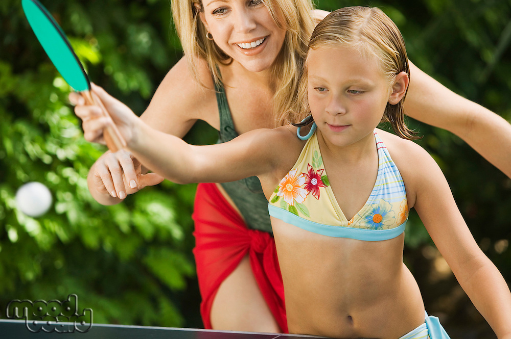 Girl (7-9) Playing Ping-Pong with Mother.