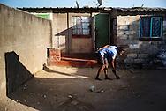 Zimbabwe, kvinde fejer foran sit hus.