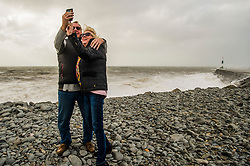 © London News Pictures. 16/10/2017. Aberystwyth, UK. A couple take a selfie as the remnants of storm system Ophelia, with Hurricane Force 12 winds gusting up to 80mph,  batter the sea defences at Aberystwyth on the Cardigan Bay coast of the Irish Sea in west Wales. The Met Office has issued an Amber weather warning, with a good chance that power cuts may occur, with the potential to affect other services, such as mobile phone coverage.. Photo credit: Keith Morris/LNP