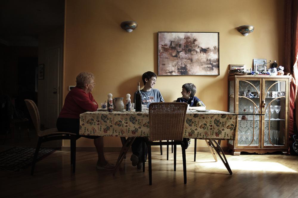 Nonna seduta a tavola con i suoi nipoti.<br /> Tutti i giorni gli prepara il pranzo e li attende a casa mentre tornano da scuola.<br /> <br /> Grandmother sitting at table with her grandchildren.<br /> Every day grandmother prepares lunch for her grandchildren.