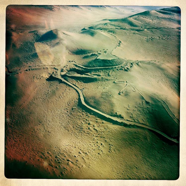 """Imagen aerea donde se puede apreciar el camino en medio del desierto hasta la mina San Jose. Plan B, es un ensayo fotografico basado en aquellas cosas que la mirada somera no permite ver, de los días de espera, angustia, soledad y fe que las familias de los 33 hombres atrapados en la mina San Jose dejaron en el paisaje arido del desierto de Atacama tras el esperado rescate. """"Plan B"""", tambien es un acto de fe personal, por intentar plasmar en un relato diferente, sin más pretensión que la mirada interna a los sentimientos que esa montaña atrapó implacable y para siempre, pero que bajo la mirada superficial de los medios no permite escudriñar por tratarse de pequeños fragmentos que apelan a emociones individuales y no a la masividad que persiguen los reportes de prensa. Este ensayo es una invitación abierta a descubrir los pequeños milagros que florecieron en la montaña y en el día a día de cada una de las familias que nunca dejaron de creer en la vida, aun así se enfrentaran a la inmensidad del desierto y a las minimas espectativas de vida que el lugar entregaba.""""Plan B"""", esta constituido por fotografías ejecutadas en su totalidad con un telefono iPhone 4 y la aplicacion Hipstamatic. ROBERTO CANDIA / REVISTA NUESTRA MIRADA"""