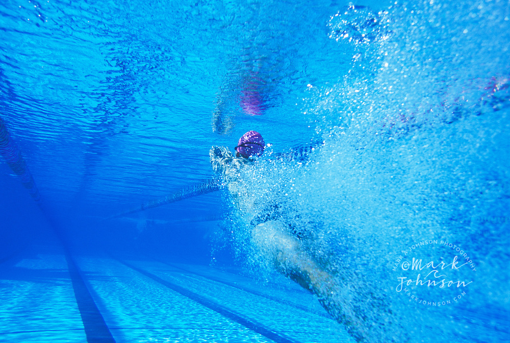 Male swimmer diving into pool