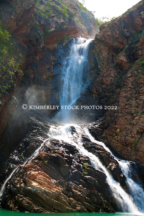 Sunlight hits the water at Turtle Falls in Dugong Bay on the Kimberley coast.  Water cascades down the falls at the end of the Kimberley wet season.