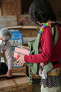 A mother with a small baby is collecting a packet of brownies at Bridge for Fukushima, an NPO that are helping parents with young children in Minamisoma, 20 km from the nuclear power plant. Fuksuhima, Japan.