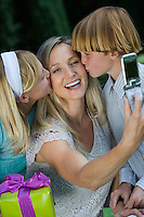 Mid-adult woman taking photograph with mobile phone of her with two children