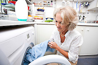 Senior woman loading washing machine at home
