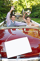 Happy newlyweds waving in convertible with blank sign in foreground