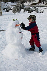 California, Lake Tahoe: Child makes a snow man at  North Lake Tahoe Regional Park.  Photo copyright Lee Foster.  Photo # cataho107583