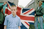 Lee and Paul holding a Union Jack flag behind Neville, Hawthorne Road, High Wycombe, UK, 1980s.
