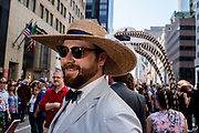 New York, NY - April 16, 2017. A bow-tied man wearing a wide-brimmed straw hat with long sweeping feathers New York's annual Easter Bonnet Parade and Festival on Fifth Avenue.