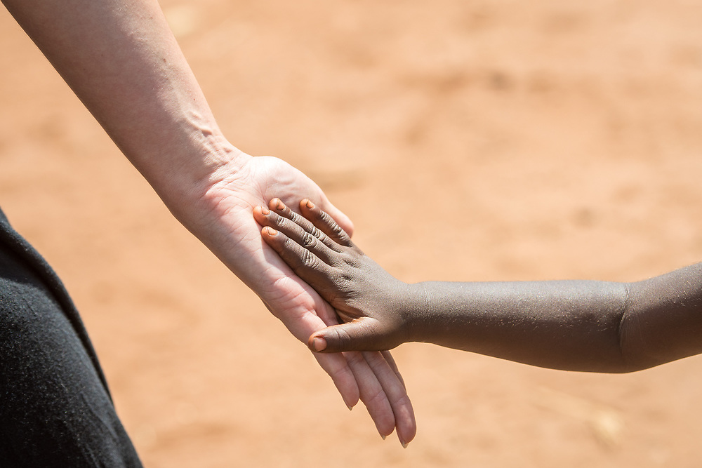 Hand of young Zambian child lightly placed against adult Caucasian woman, Mukuni Village, Zambia