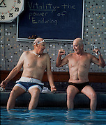 Two elderly men show off their fitness to each other as they laugh about the moment and the sign behind them. Taken during a workout at the YMCA in Sacramento.